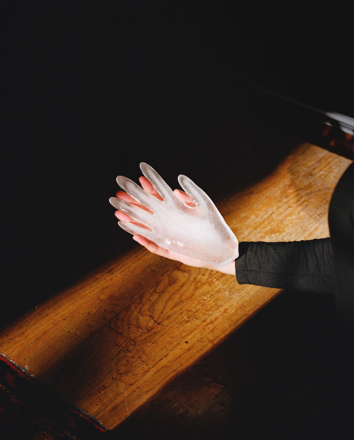 Black image with a dramatically lit wooden plank background. An arm in a black long sleeve shirt is coming in from the left side of the image and the hand is holding an ice block in the shape of a hand.