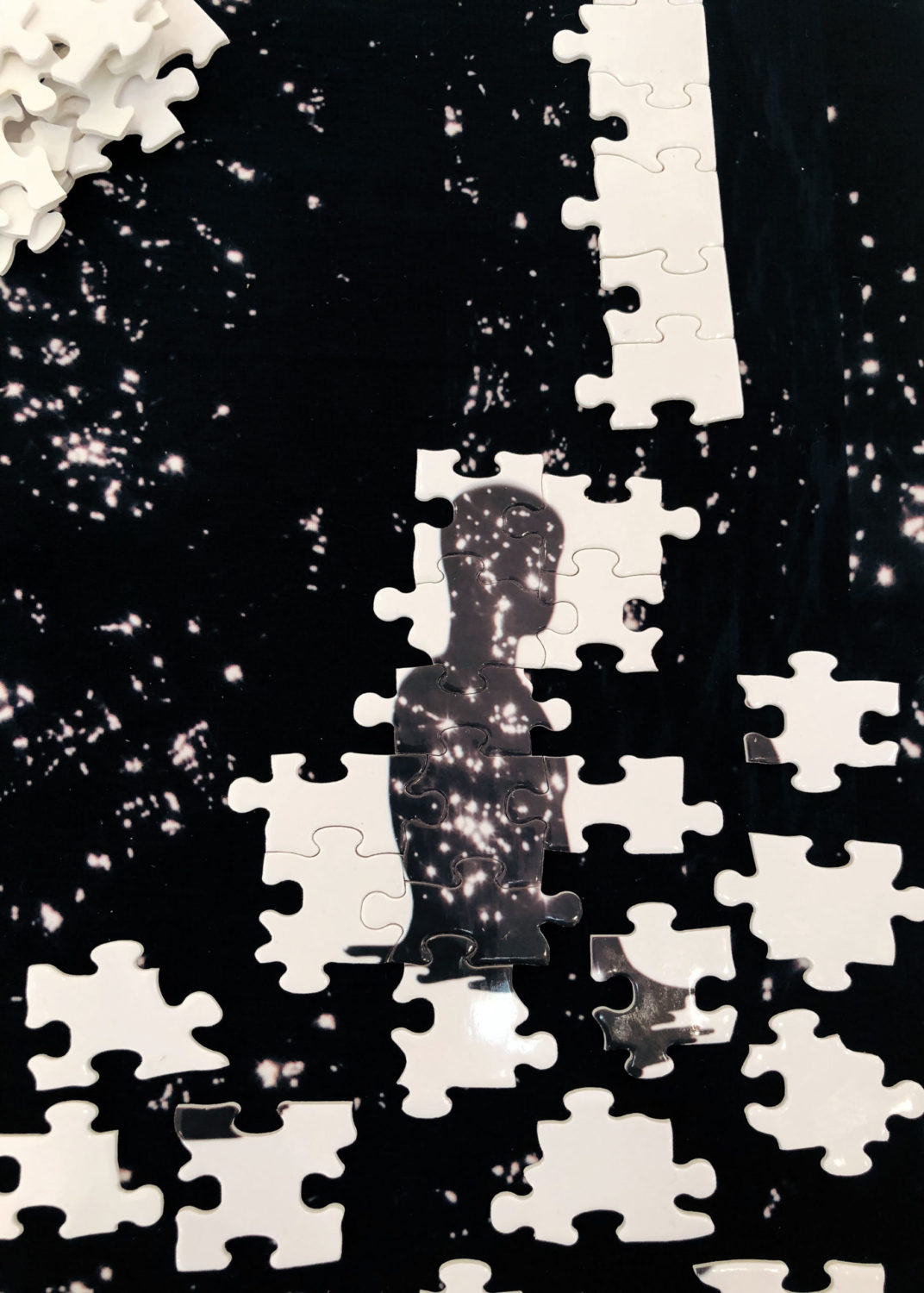 Black background with spotted light leeks (white) An unfinished puzzle is in the foreground. There is a human figure in black made printed on the white puzzle